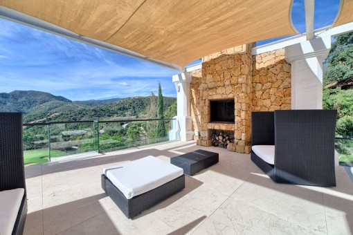 Terrace with barbecue site fireplace and glass balustrade