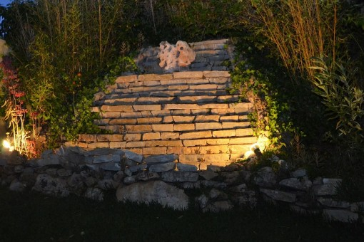 The illuminated slope with stone wall at night