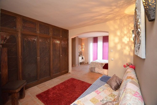 The master bedroom offers a wooden wardrobe and a couch